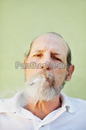 aged caucasian man smoking cigarette