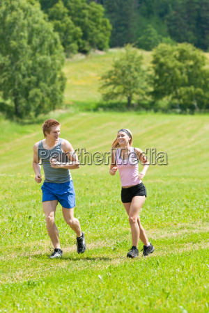 sportive young couple jogging meadows sunny