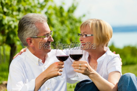 happy couple drinking wine by the