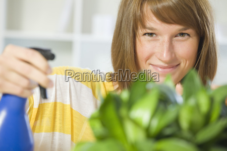 woman watering plants at home