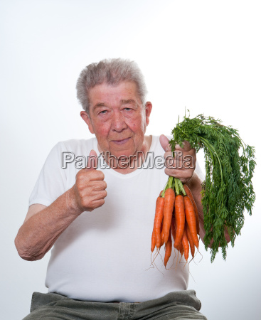 senior holding carrots in his hand