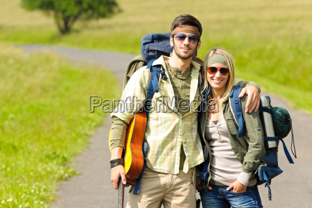 hiking young couple backpack tramping asphalt