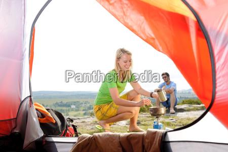 camping junges paar ausserhalb zelt kochen