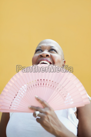 mature african woman with fan smiling