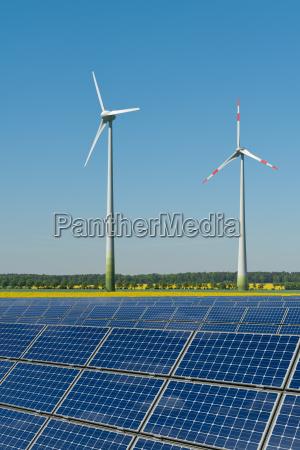 windkraftraeder und solarmodule vor einem rapsfeld