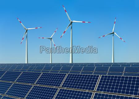 windkraftraeder und solarmodule vor blauem himmel