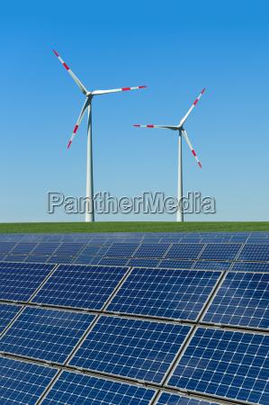 solarmodule und windkraftraeder in einem feld