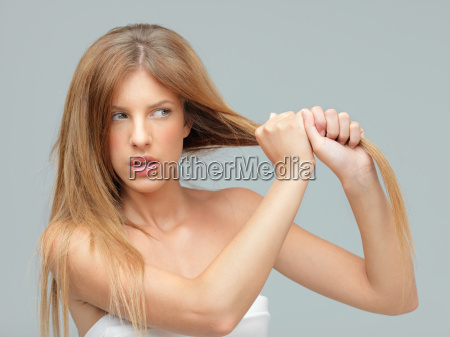 young woman pulling her damadged hair