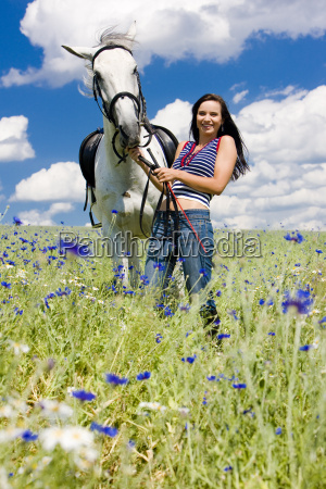 equestrian with a horse on meadow