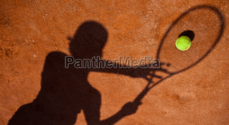 skygge af en tennisspiller i aktion