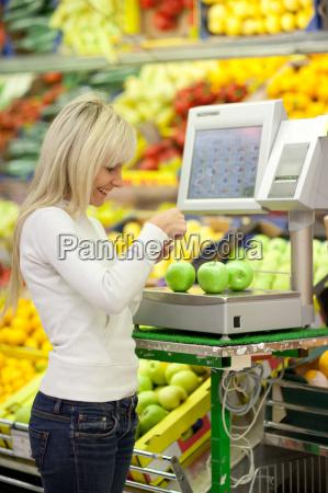 schoene junge frau einkaufen fuer obst