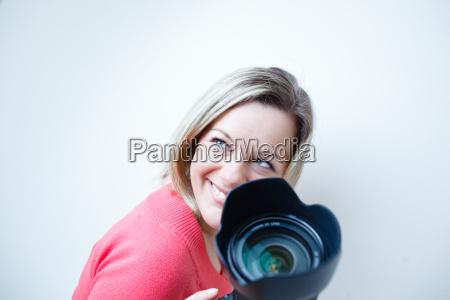 huebsche fotografin mit ihrer digitalkamera farbfarbiges