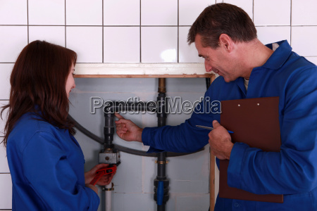 a mature plumber teaching to a