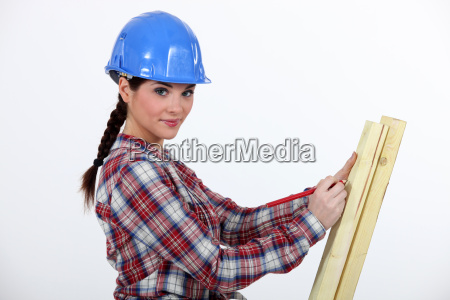 female carpenter taking measurements of a