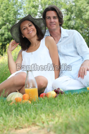couple sitting on the grass eating