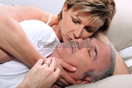 frau kuesst ihren schlafenden mann