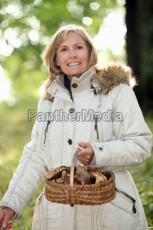 a mature woman holding a mushroom