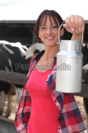weiblicher landwirt der die kuehe melkt