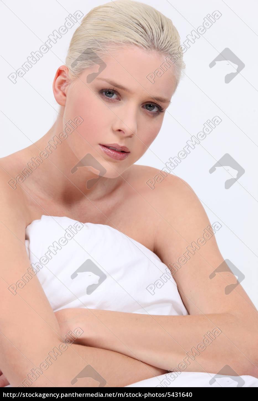 blonde frau nackt sitzung vom bett mit einem neutralen ...