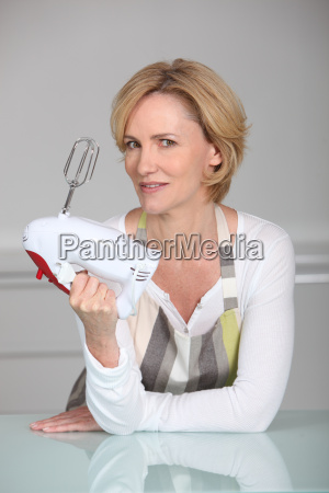 woman wearing apron holding electric whisk