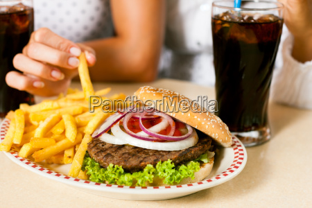 two women eat hamburgers and drink