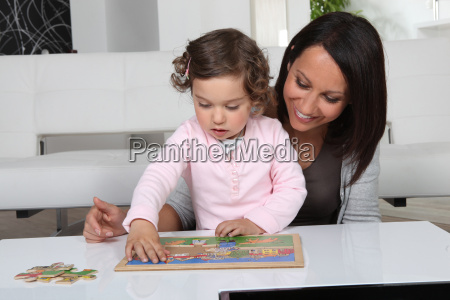 little girl and woman doing puzzle