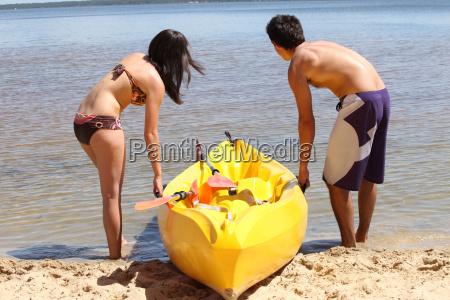 young couple dragging their kayak onto