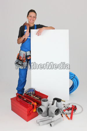 smiling female plumber with panel for