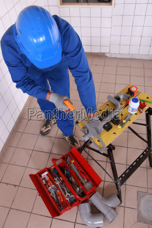 top view of plumber cutting pipe
