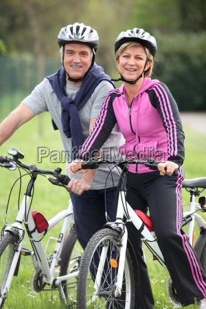 cheerful mature couple having a bike