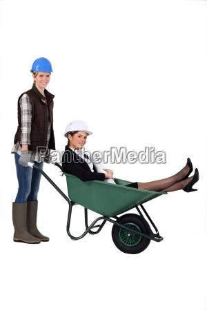 an architect getting a wheelbarrow ride