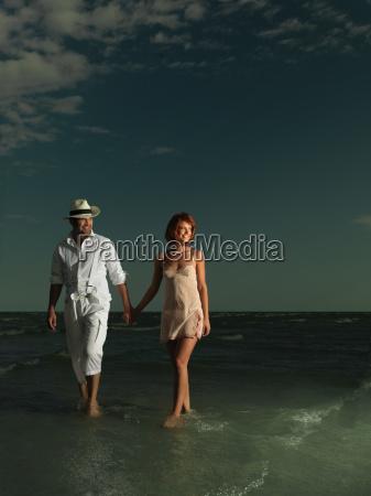 young happy couple walking on sea
