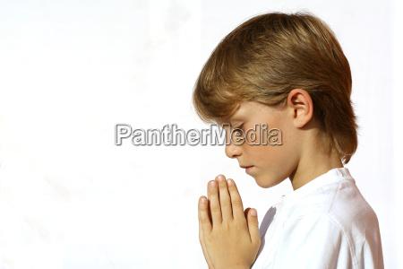 christian child praying hands clasped