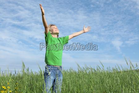 happy child arms raised praising the