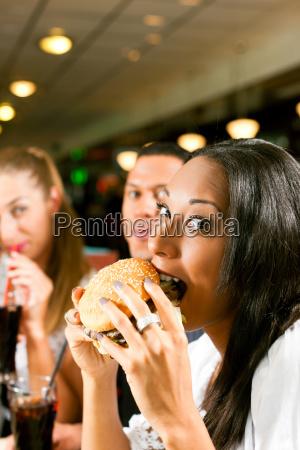 freunde essen fastfood in einem restaurant