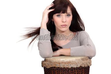 schoene frau spielt auf traditionellen trommeln