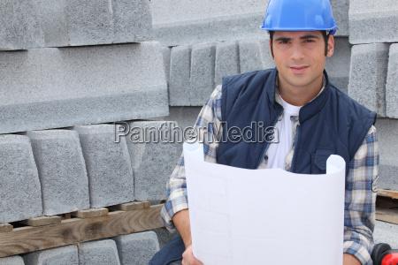 bauarbeiter neben paletten betonbordstein stehen waehrend