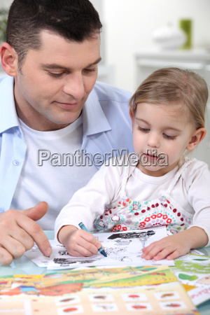 little girl colouring under dad039s watchful