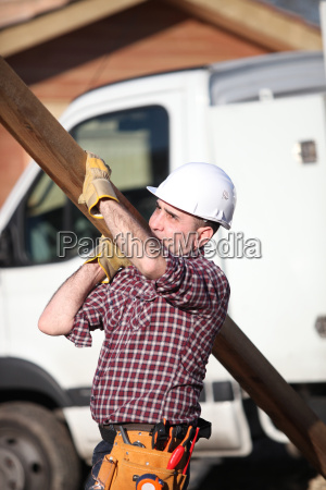 construction worker carrying a heavy plank