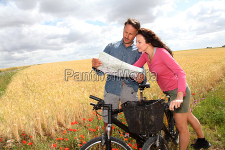 couple riding looking at map on