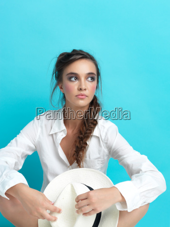 young woman blue background white hat