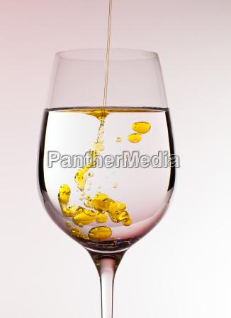 olivenoel wird in weinglas gegossen