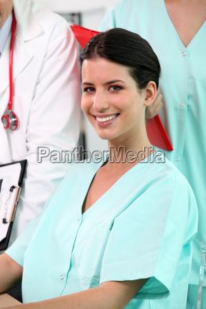 strahlend brunettekrankenschwester sitzt am schreibtisch mit
