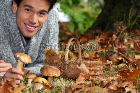 man gathering mushrooms and chestnuts in