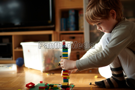 boy builds with lego blocks