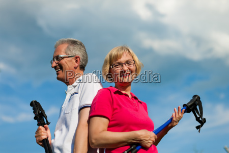 happy senior couple nordic walking in