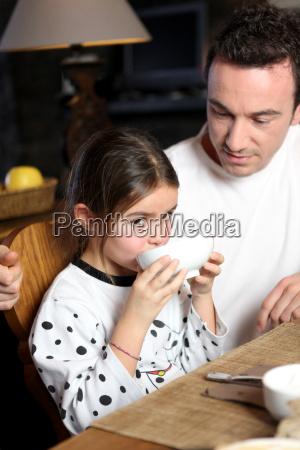 man with little girl having breakfast