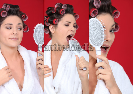 bruenette traegt bademantel mit lockenwickler haarbuerste