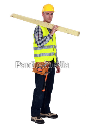 craftsman carrying two wooden boards on