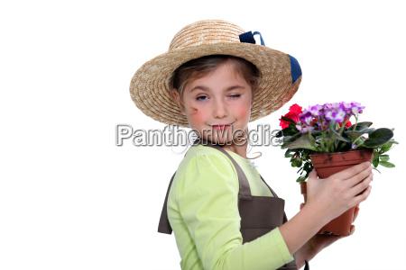 little girl wearing straw hat holding